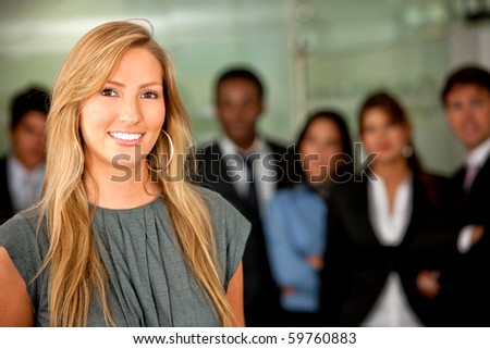 Business woman at the office with a group behind - stock photo