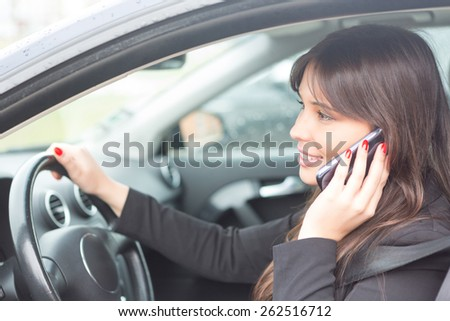 Business woman at the phone while driving - stock photo