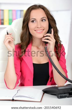 Business woman at work. Confident young business woman talking on the phone while sitting at her working place