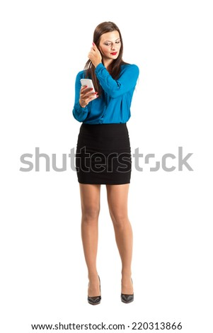 Business woman checking her hair by looking on her mobile phone reflection or photo. Full body length isolated over white background. - stock photo
