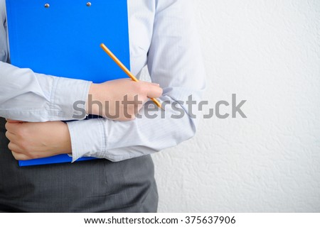 Business woman close up. Folder and pencil in hand - stock photo