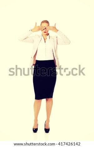 Business woman covering her eyes with her hands. See no evil concept - stock photo
