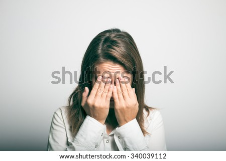 Business woman covers her face with her hands. studio photo on a gray background - stock photo