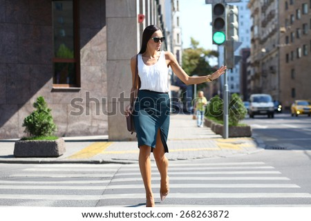 Business woman crossing the road outside in sunny weather - stock photo