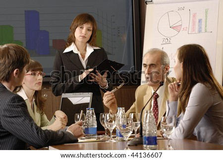 business woman demonstrating report to colleagues - stock photo
