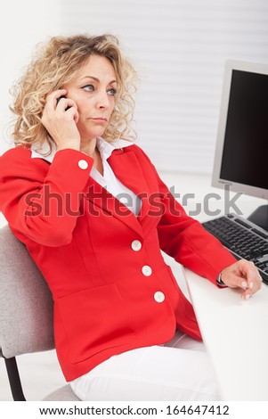 Business woman disappointed by a telephone conversation - sitting by her desk - stock photo