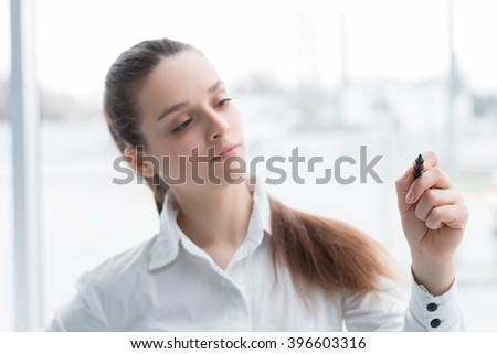 Business woman drawing a concept diagram on transparent screen