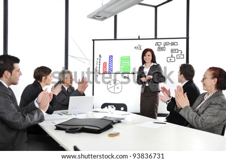 Business woman drawing a diagram during the presentation and receiving applause - stock photo