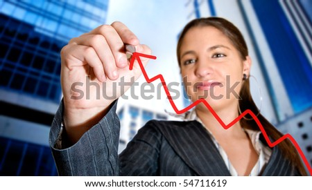 Business woman drawing a graph in the city - stock photo