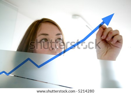 business woman drawing a graph on a glass window in an office - focus is on graph - stock photo