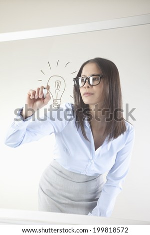 Business woman drawing light bulb