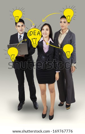 Business woman drawing light bulb with her business team