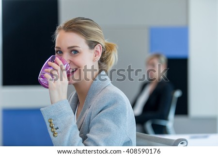 Business woman drinking a glass of water - stock photo
