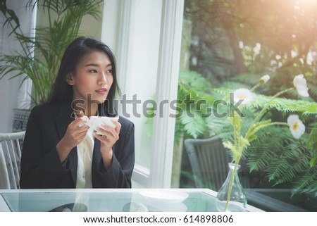 Business woman drinking coffee in cafe