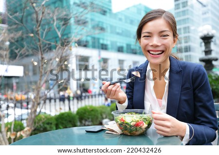 Business woman eating salad on lunch break in City Park living healthy lifestyle. Happy smiling multiracial young businesswoman, Bryant Park, Manhattan, New York City, USA - stock photo