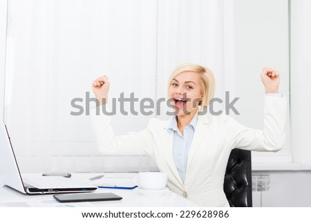Business woman excited hold fist hands up raised arms sitting at modern office desk, surprised happy smile businesswoman success - stock photo