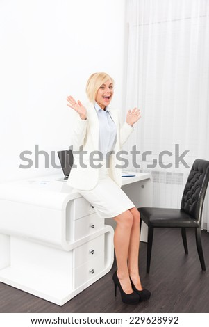 Business woman excited hold hands up raised arms sitting at modern office desk, surprised happy smile businesswoman success - stock photo