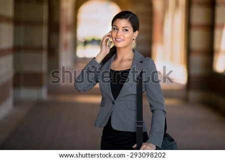 Business woman executive walking and talking on the cell phone - stock photo