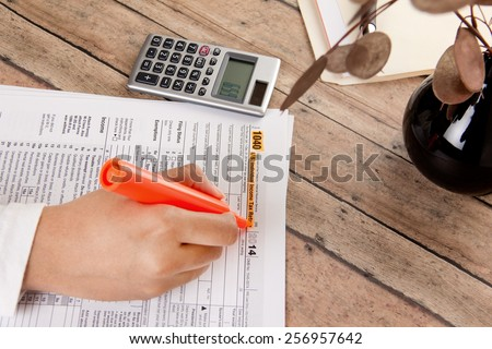 business woman filing federal income tax form 1040 - stock photo