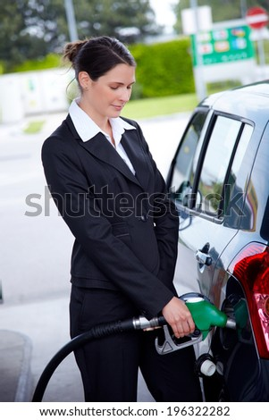 business woman filling car at gas station - stock photo