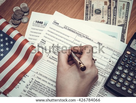 Business woman fills the tax form 1040 with money, pen, flag of USA and calculator. toned image - stock photo
