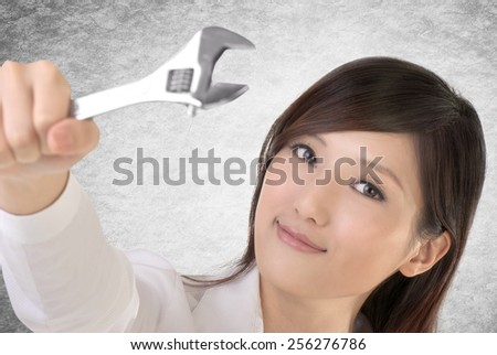 Business woman fix by using wrench. - stock photo