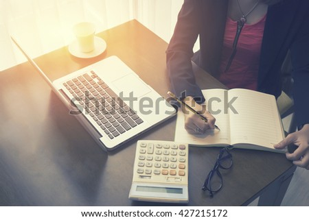 Business Woman freelancer female hands with pen writing on notebook at home  office or coffee cafe,hands with pen writing note,writing with pen and reading books at table,selective focus,vintage color - stock photo