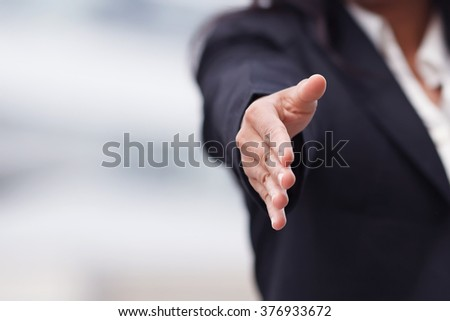 Business woman giving a handshake.