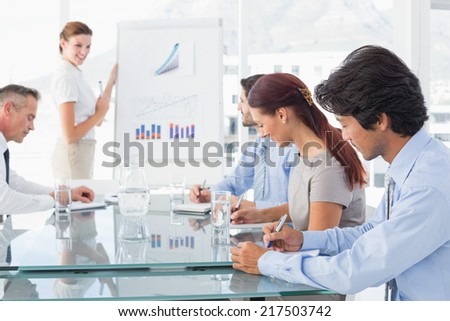 Business woman giving a presentation to her team - stock photo