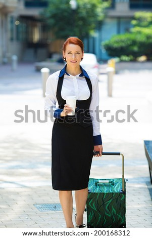 Business woman going on trip. Portrait businesswoman, company employee, attractive corporate executive, young model crossing street, traveling with luggage, handbags in the city, holding cup of coffee - stock photo