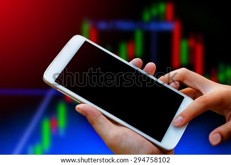 business woman hand hold and touch screen on smart phone,tablet,cellphone over blur  stock chart market background,with filtered red and green color,abstract background to forex and stock concept.  - stock photo