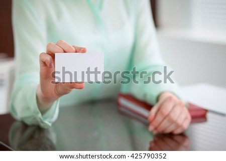 Business woman hands in a green blouse sitting at a desk in an office and holds out business card.