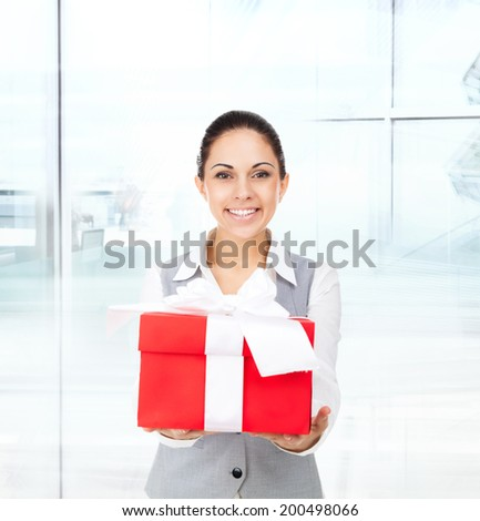Business woman happy smile hold red gift box in hands. Businesswoman in modern office - stock photo