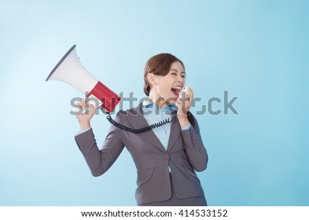 Business woman happy with a megaphone isolated on blue background, model is a asian beauty - stock photo