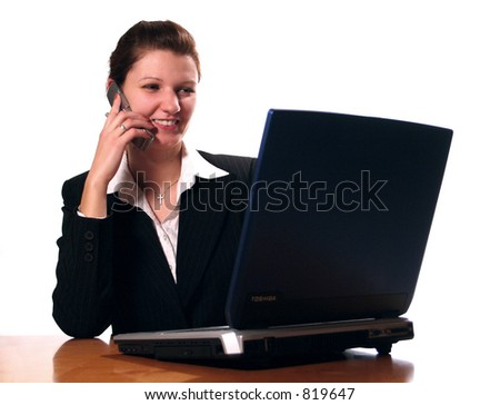 Business woman hard at work on her laptop computer with a cell phone. (happy)