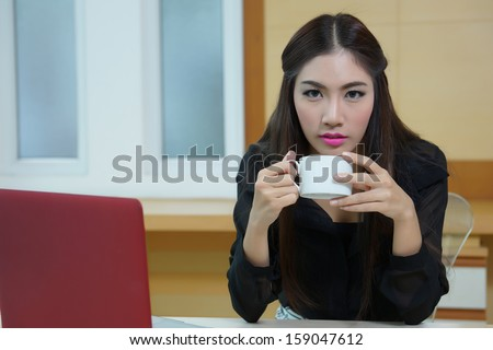 Business woman hold cup of coffee sitting at the desk with laptop - stock photo