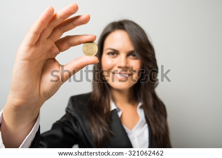 Business woman holding a coin - stock photo