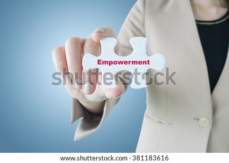 Business woman holding a piece of jigsaw puzzle with word Empowerment