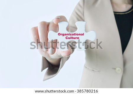 Business woman holding a piece of jigsaw puzzle with word Organizational Culture - stock photo