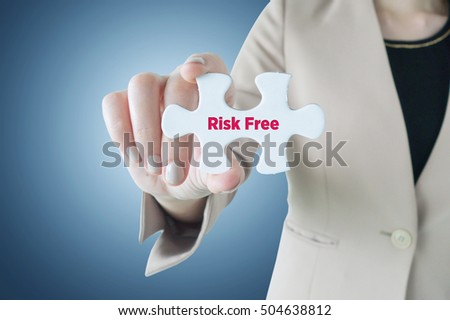Business woman holding a piece of jigsaw puzzle with word Risk Free