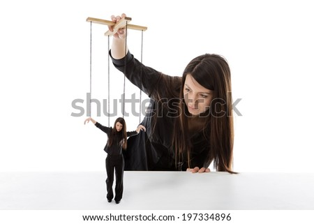 business woman holding a puppet of herself pulling strings