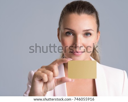 Business woman holding credit card against her lips isolated studio portrait