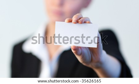 Business woman holding out a business card with the camera focus pin sharp on the card - stock photo