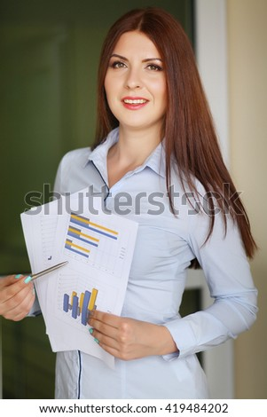 business woman holding reports and looking at camera. Copy space - stock photo