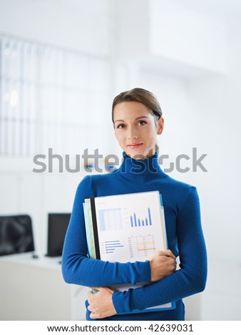 business woman holding reports and looking at camera. Copy space
