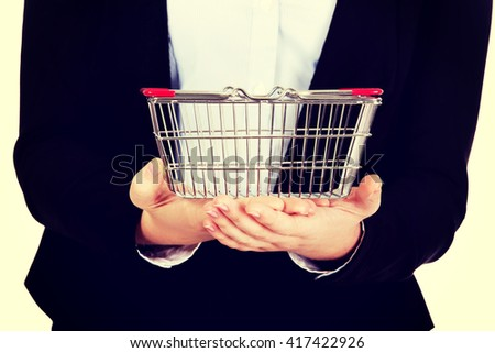 Business woman holding shopping cart - stock photo