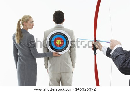 Business woman holding target to man's back while other man aims bow and arrow - stock photo