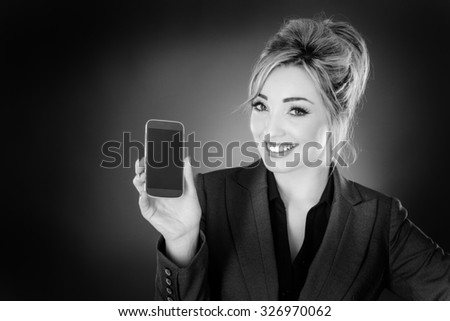 business woman holding up a mobile phone and showing you the screen shot in the studio on a gray background.