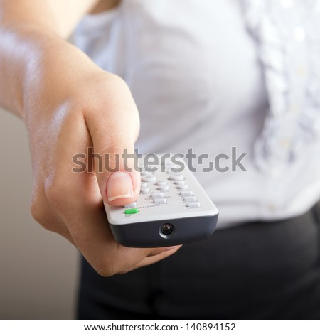 Business woman holds a remote control in her hands with her body out of focus - stock photo