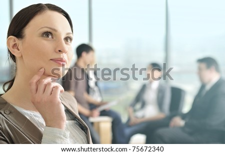Business woman in an office environment with large stained-glass window on background - stock photo